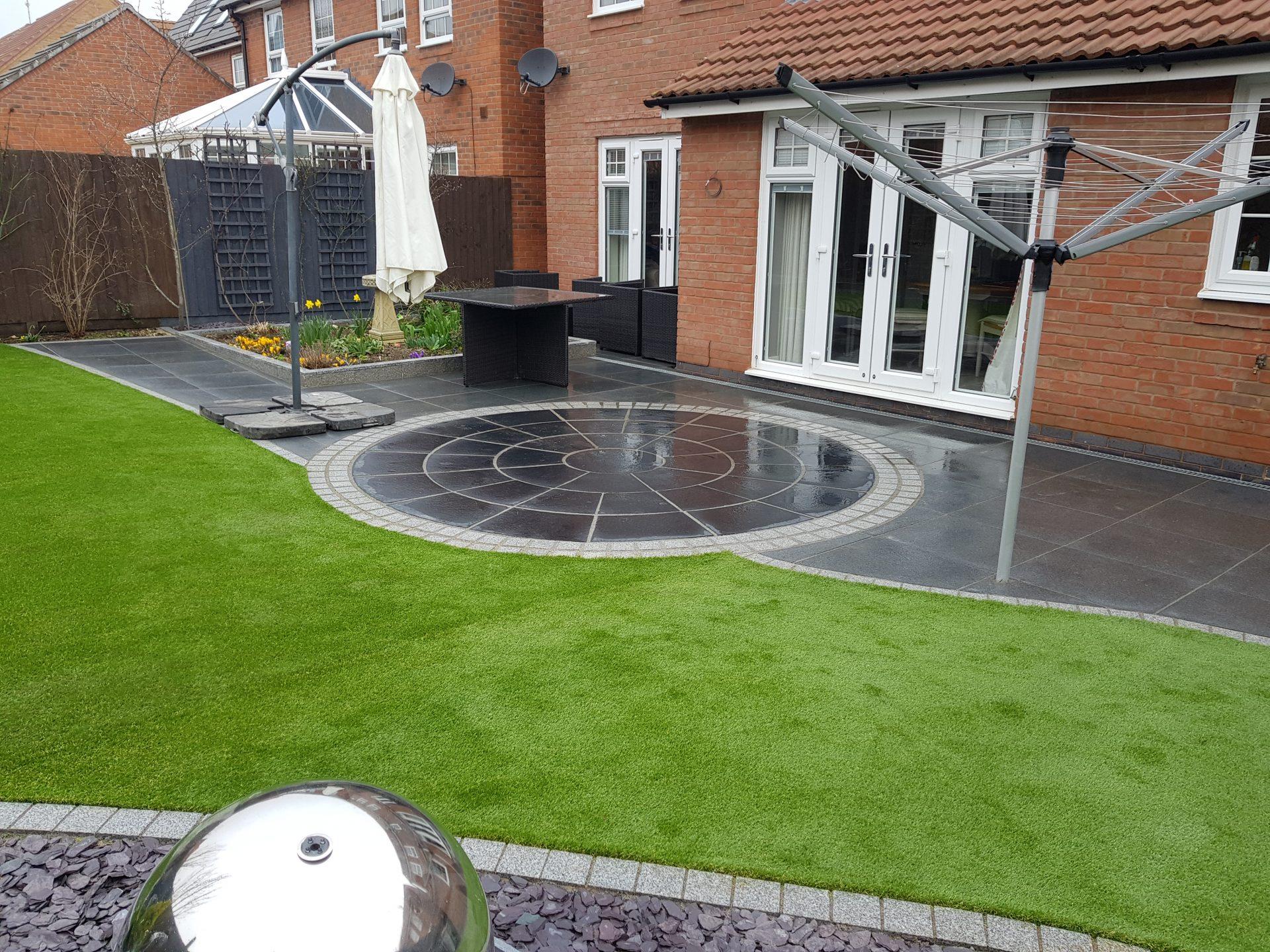 Dark grey circular patio area, artificial grass laid and plum slate