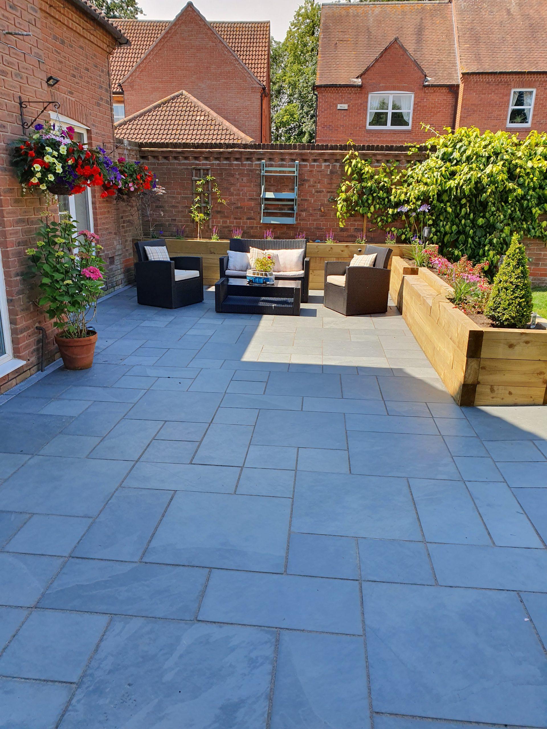Garden patio seating area with wooden sleeper raised borders