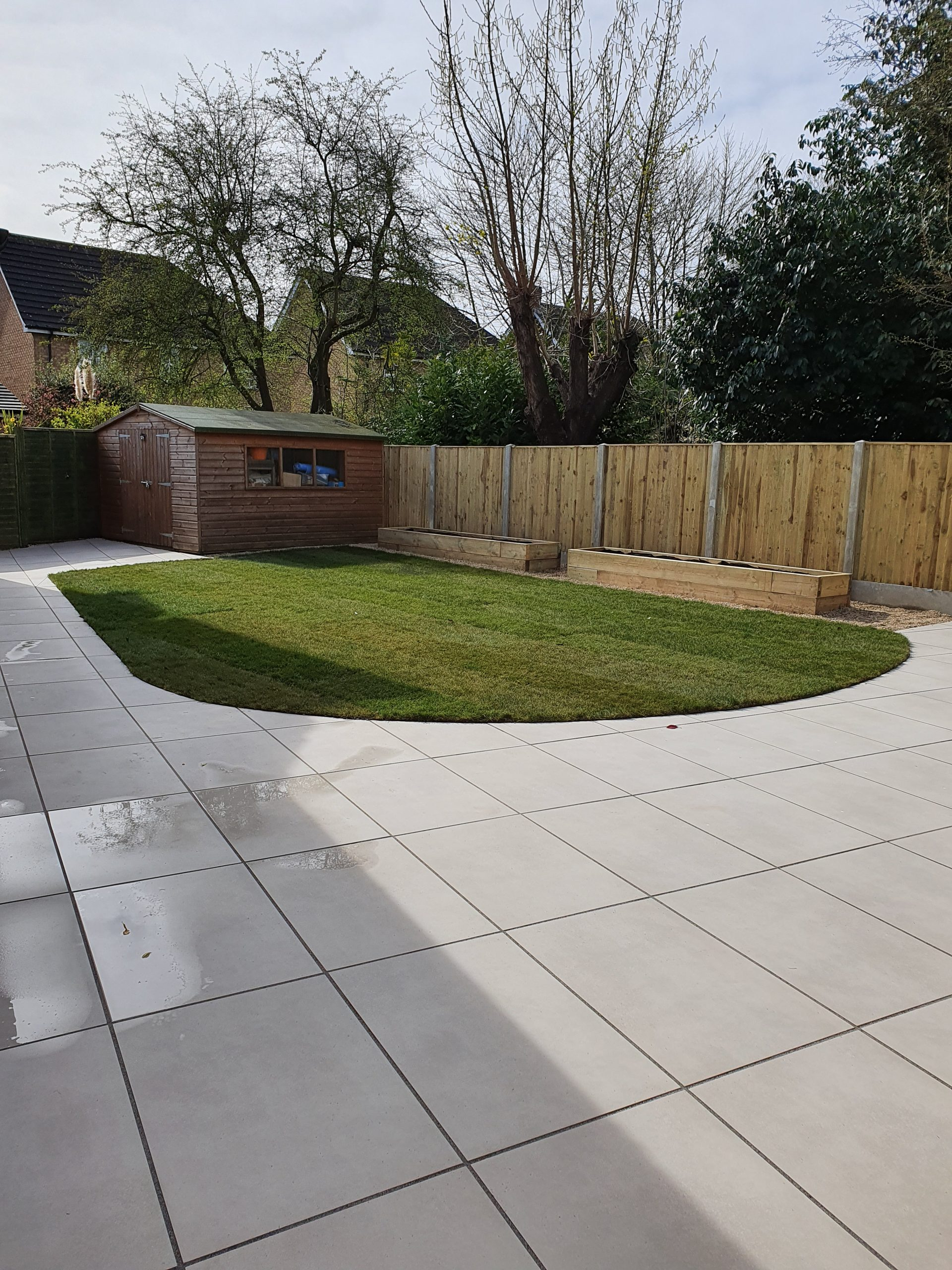 Light coloured slabbed landscaped garden, raised borders and fencing