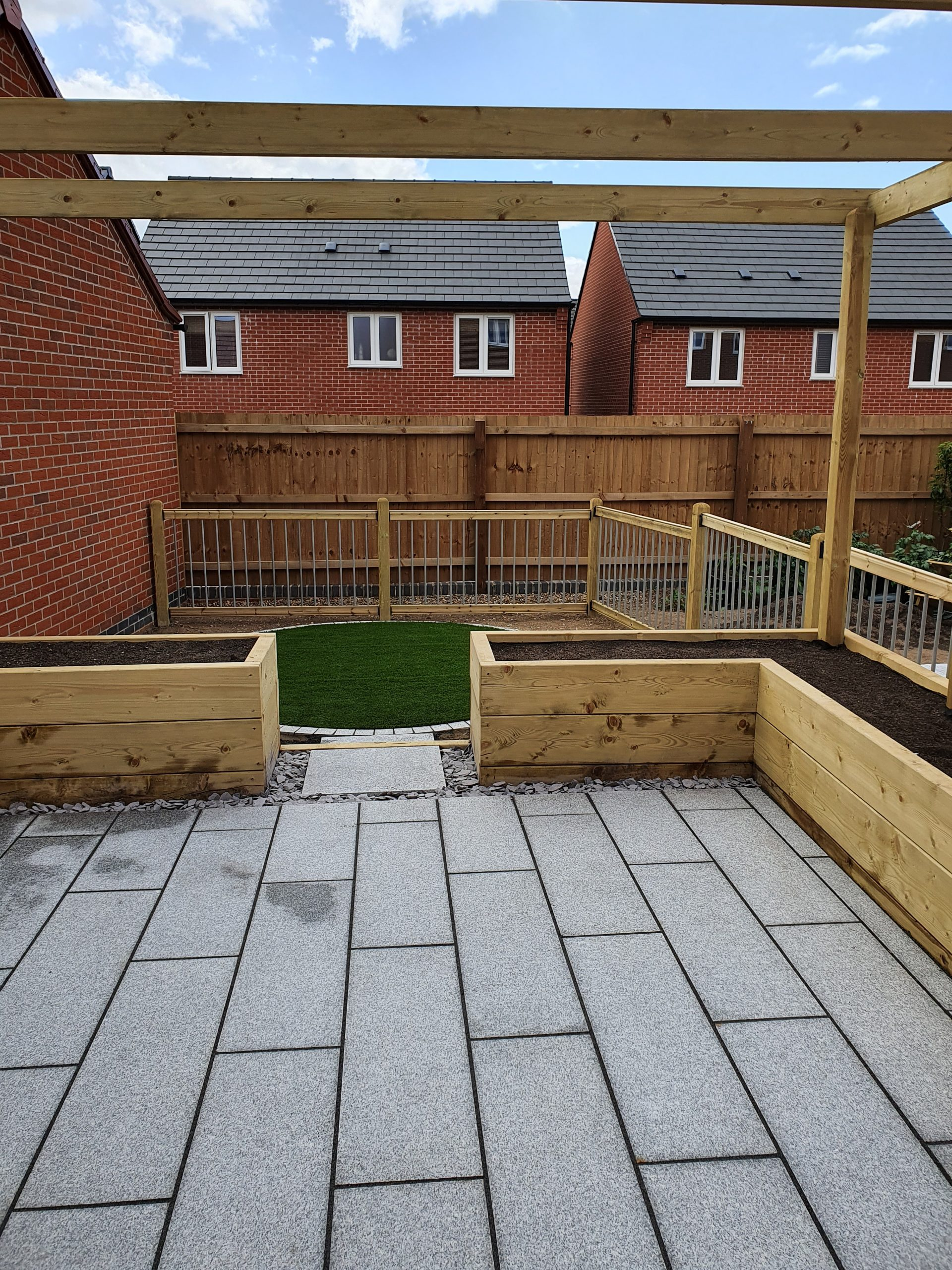 Wooden timber pergola, sleeper raised planters, railings and grey patio area