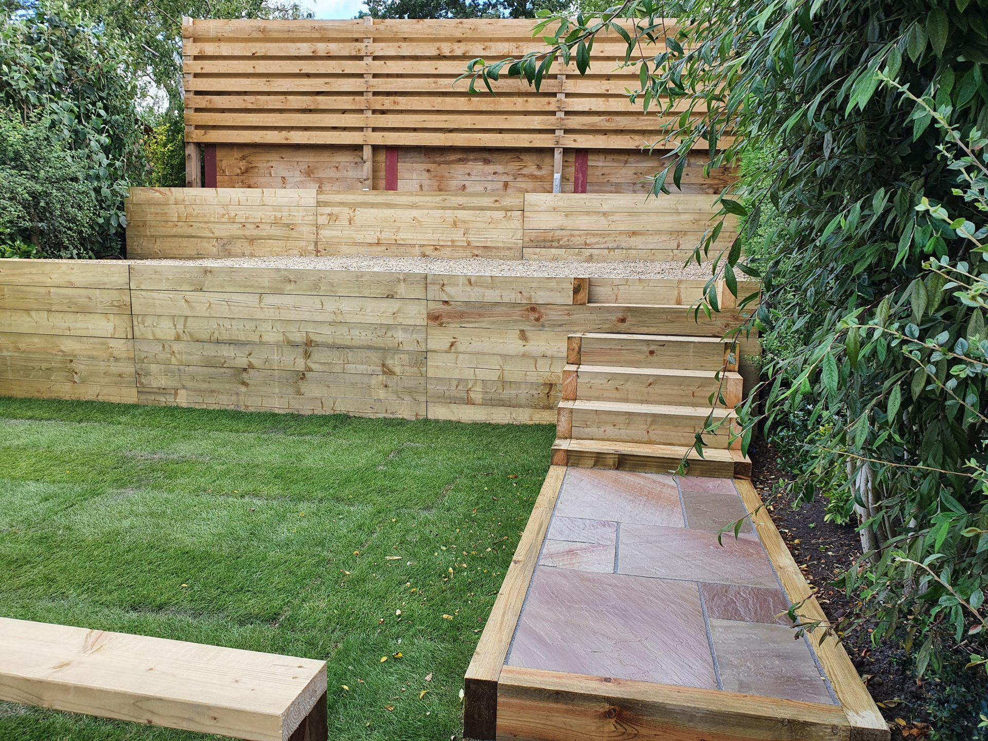 Tiered multi level garden wooden sleeper retainer walls, steps and newly laid turf