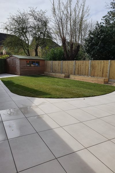 Garden make over, light coloured slabs, curved lawn, fencing and wooden raised planters